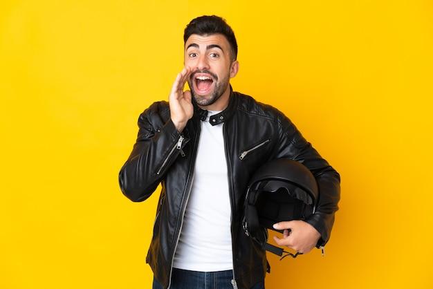 口を大きく開いて叫んで孤立した黄色の壁の上にオートバイのヘルメットを持つ白人男性