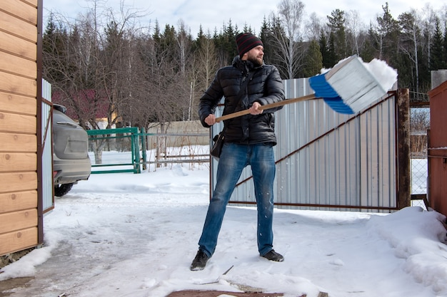 Caucasian man with a beard in a black jacket blue jeans and a black hat cleans snow in a parking lot