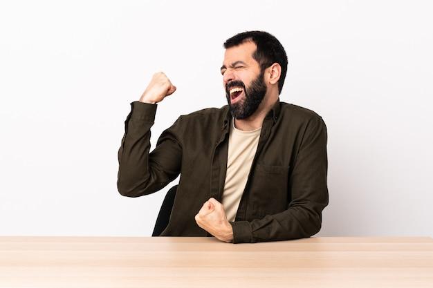 勝利を祝うテーブルでひげを持つ白人男。