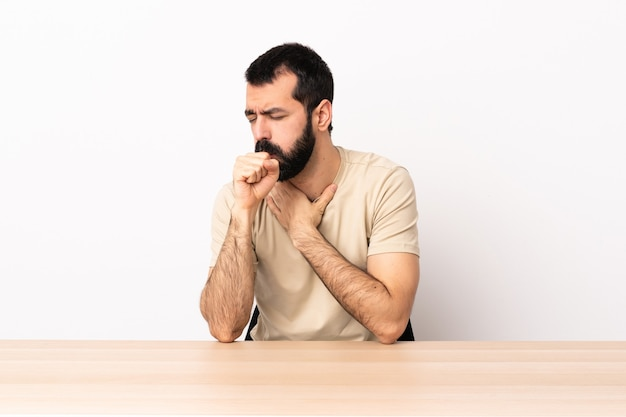 기침을 많이하는 테이블에 수염을 가진 백인 남자.
