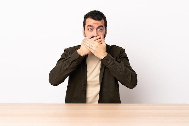 손으로 입을 덮고 테이블에 수염을 가진 백인 남자.