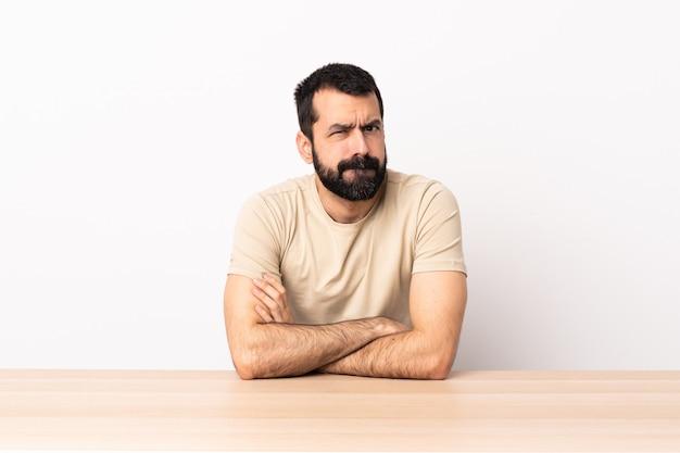 動揺してテーブルのひげを持つ白人男。