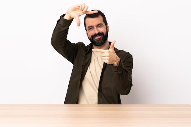 얼굴을 집중 테이블에 수염을 가진 백인 남자. 프레임 기호.