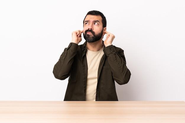 欲求不満で耳を覆っているテーブルにひげを生やした白人男性。