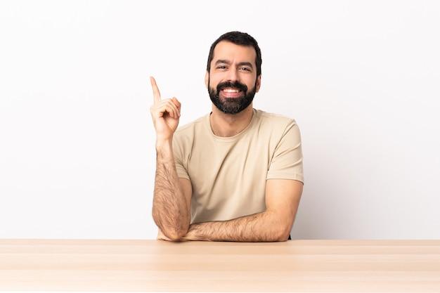 Кавказский мужчина с бородой в таблице счастлив и указывая вверх.