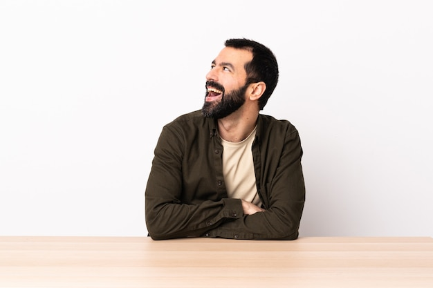 행복 하 고 웃 고 테이블에 수염을 가진 백인 남자.