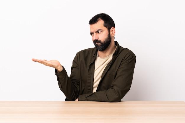 疑問を持つcopyspaceを保持しているテーブルでひげを持つ白人男。