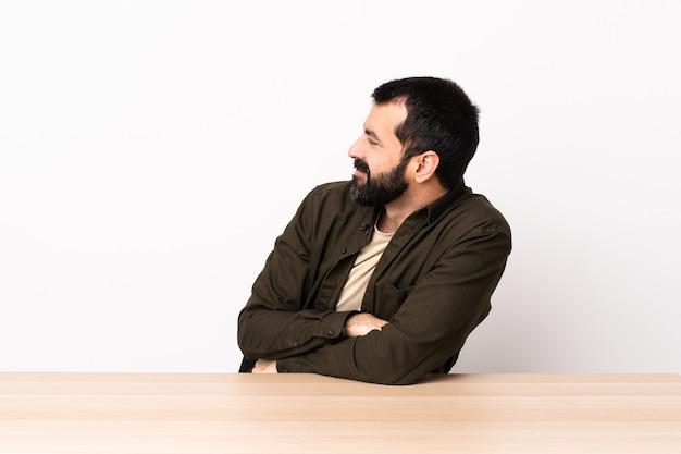 横向きのテーブルにひげを生やした白人男性。