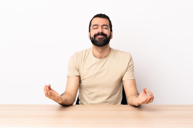 젠 포즈에서 테이블에 수염을 가진 백인 남자.
