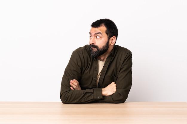 측면을 찾고 의심 제스처를 만드는 테이블에 수염을 가진 백인 남자.