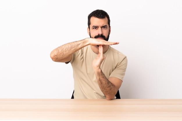 Кавказский мужчина с бородой в таблице делая жест тайм-аут.