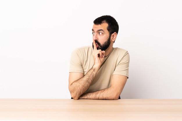 口の中に指を入れて沈黙ジェスチャーの兆候を示すテーブルでひげを持つ白人男