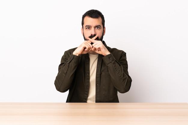 침묵 제스처의 표시를 보여주는 테이블에 수염을 가진 백인 남자.
