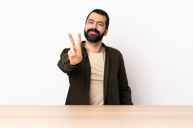 웃 고 승리 기호를 보여주는 테이블에 수염을 가진 백인 남자.