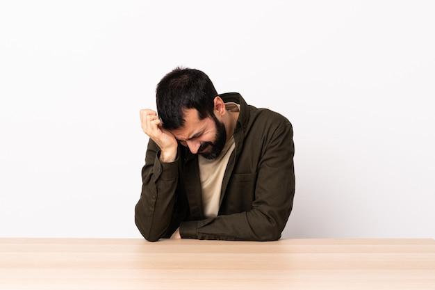 頭痛を持つテーブルでひげを持つ白人男