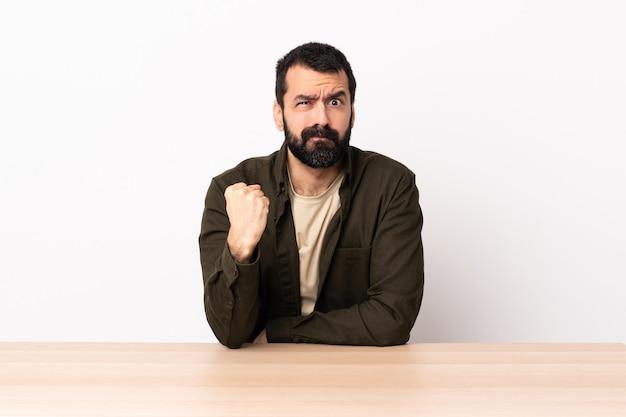 不幸な表情を持つテーブルでひげを持つ白人男