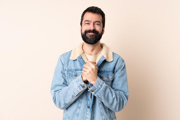 Кавказский мужчина с бородой на изолированном фоне смеется