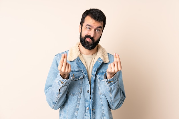 Caucasian man with beard over isolated background making money gesture but is ruined
