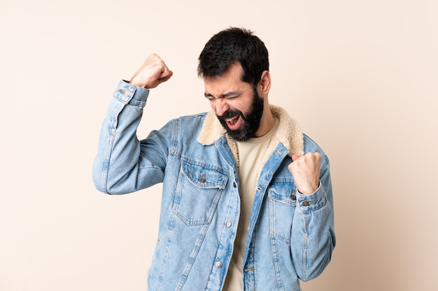 Caucasian man with beard over isolated space celebrating a victory