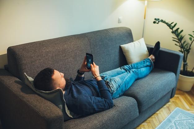 モバイルでいくつかのビデオを見ながらソファに横たわっているひげを持つ白人男性