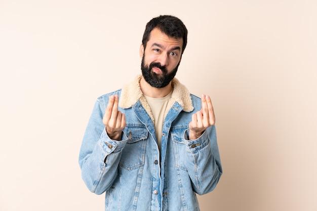 Кавказский мужчина с бородой на изолированном фоне делает денежный жест, но разрушен