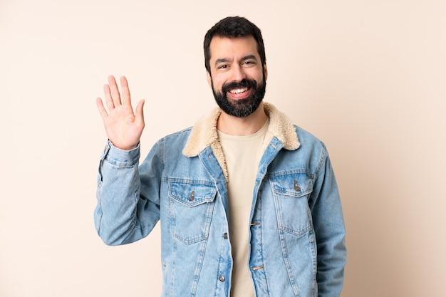행복 한 표정으로 손으로 경례 고립 된 벽 위에 수염을 가진 백인 남자
