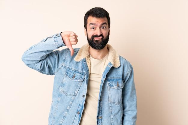 부정적인 표현으로 아래로 엄지 손가락을 보여주는 고립 된 벽 위에 수염을 가진 백인 남자