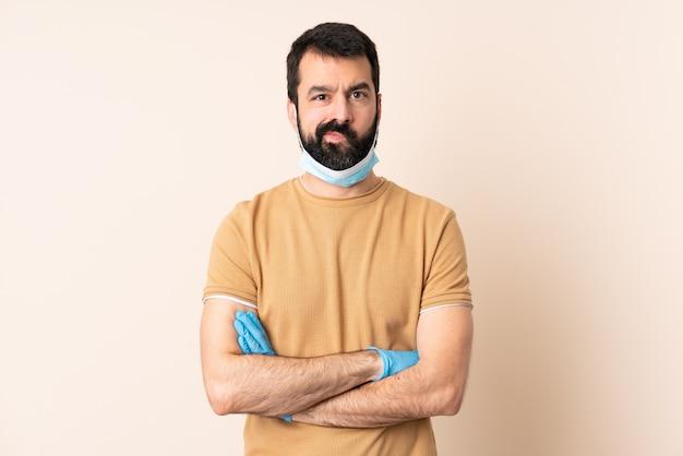 壁の動揺をマスクと手袋で保護するひげを持つ白人男