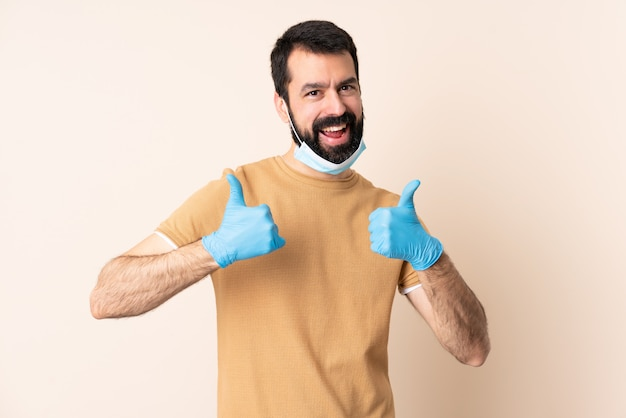 Caucasian man with beard protecting with a mask and gloves over wall giving a thumbs up gesture