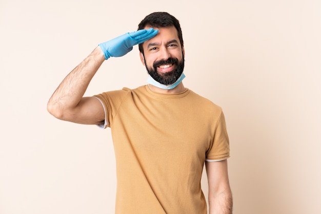 Caucasian man with beard protecting with a mask and gloves over wall saluting with hand with happy expression
