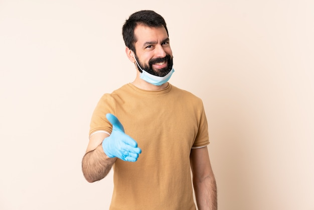 Caucasian man with beard protecting with a mask and gloves over wall shaking hands for closing a good deal