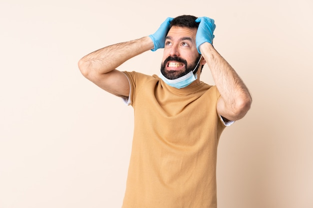 Caucasian man with beard protecting with a mask and gloves over wall stressed overwhelmed