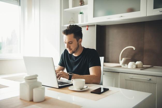 キッチンのコンピューターで休んでいるひげを持つ白人男性