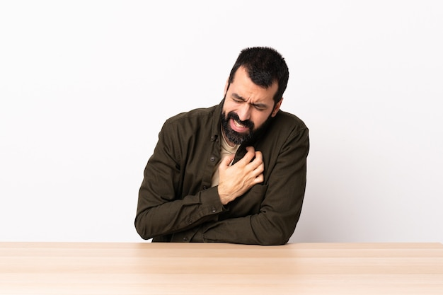 Caucasian man with beard in a table having a pain in the heart.