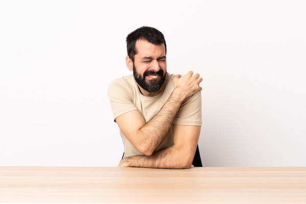 Caucasian man with beard in a table suffering from pain in shoulder for having made an effort