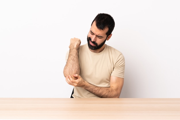Caucasian man with beard in a table with pain in elbow