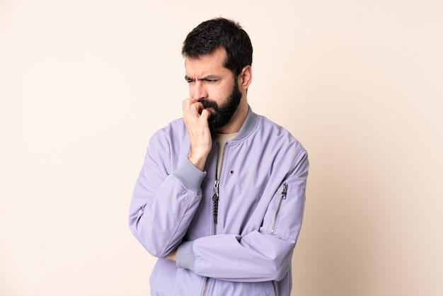 Кавказский мужчина с бородой в куртке изолирован