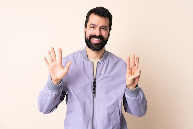 손가락으로 여덟 세 격리 된 배경 위에 재킷을 입고 수염을 가진 백인 남자