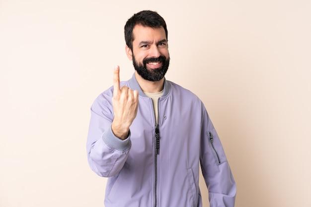 Кавказский мужчина с бородой в куртке на изолированном фоне делает приближающийся жест