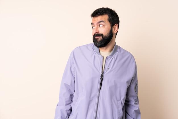 격리 된 배경 위에 재킷을 입고 수염을 가진 백인 남자 측면을 찾고 의심 제스처를 만드는