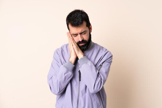 愛らしい表情で睡眠ジェスチャーを作る孤立した背景の上にジャケットを着ているひげを持つ白人男性