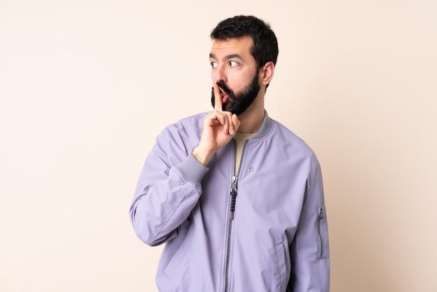 입에 손가락을 넣어 침묵 제스처의 기호를 보여주는 고립 위에 재킷을 입고 수염을 가진 백인 남자