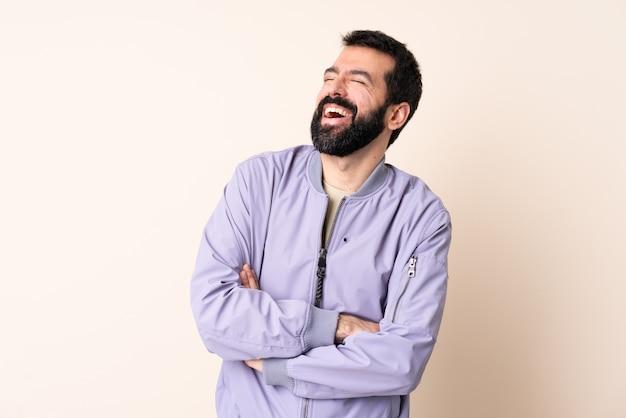 Кавказский мужчина с бородой в куртке над изолированной стеной счастлив и улыбается