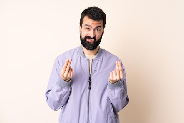 Кавказский мужчина с бородой в куртке над изолированной стеной делает денежный жест, но разрушен