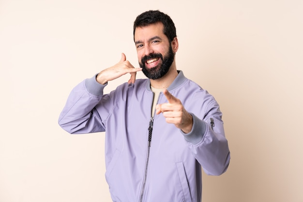 Кавказский мужчина с бородой в куртке над изолированной стеной делает жест по телефону и показывает вперед