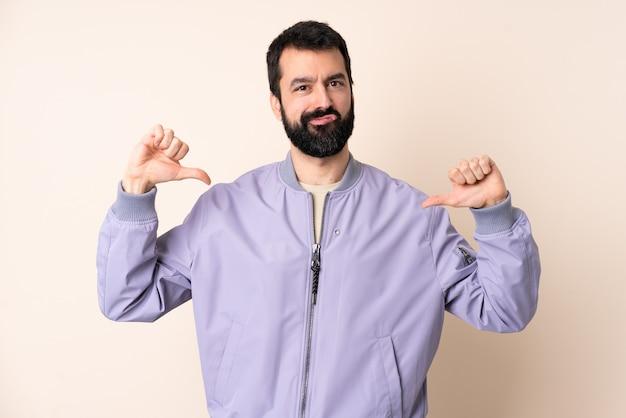 Кавказский мужчина с бородой в куртке над изолированной стеной, гордый и самодовольный