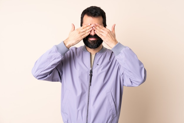 Caucasian man with beard wearing a jacket over isolated background covering eyes by hands and smiling