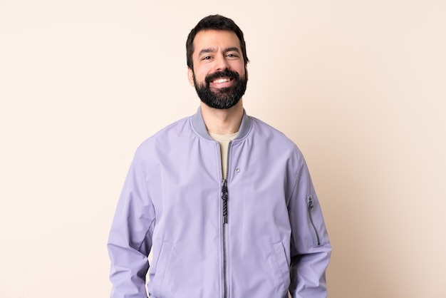 Caucasian man with beard wearing a jacket over isolated background laughing