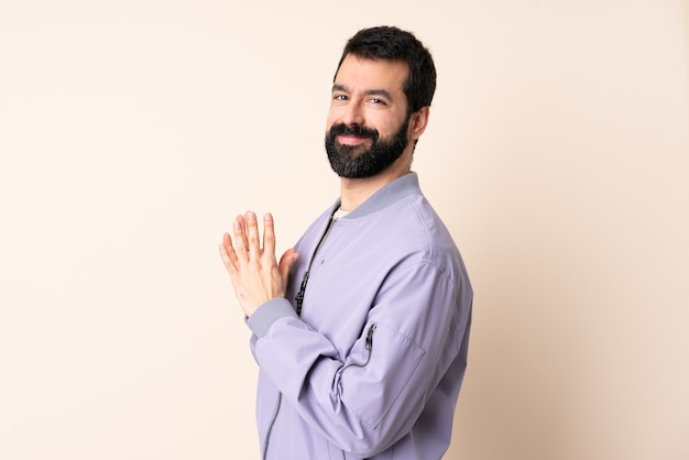 Caucasian man with beard wearing a jacket over isolated background scheming something