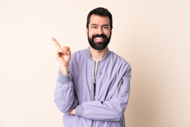 Caucasian man with beard wearing a jacket isolated happy and pointing up